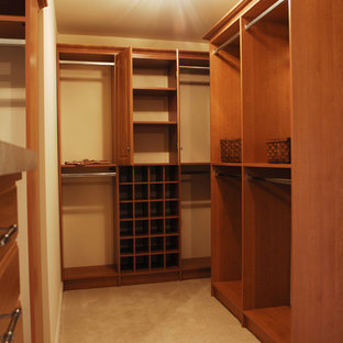 Inspiration for a mid-sized traditional gender-neutral walk-in wardrobe in DC Metro with open cabinets, medium wood cabinets and carpet.
