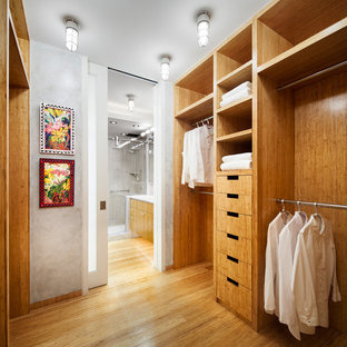 Small contemporary gender-neutral walk-in wardrobe in New York with open cabinets, light wood cabinets and bamboo floors.
