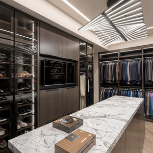 Trendy gender-neutral light wood floor and beige floor walk-in closet photo in Miami with flat-panel cabinets and dark wood cabinets