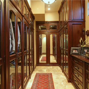 This is an example of an expansive mediterranean gender neutral dressing room in Phoenix with glass-front cabinets, light wood cabinets, multi-coloured floors and travertine flooring.