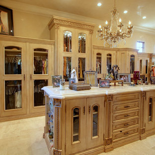 This is an example of an expansive mediterranean gender neutral dressing room in Phoenix with glass-front cabinets, light wood cabinets, travertine flooring and multi-coloured floors.