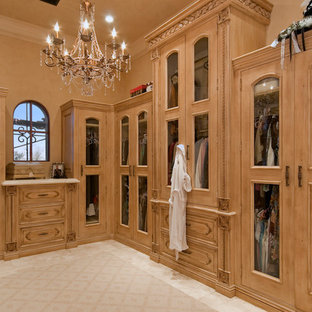 This is an example of an expansive mediterranean dressing room for women in Phoenix with raised-panel cabinets, light wood cabinets and travertine flooring.