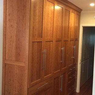 Imagen de armario de hombre, contemporáneo, pequeño, con armarios estilo shaker, puertas de armario de madera oscura y suelo de madera clara