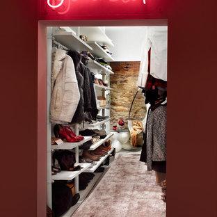 Foto de armario vestidor unisex, ecléctico, con armarios abiertos, puertas de armario blancas y suelo de madera oscura