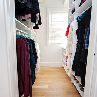 Modelo de armario vestidor tradicional renovado, de tamaño medio, con puertas de armario blancas y suelo de madera clara
