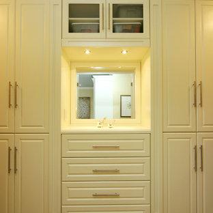 Immagine di una cabina armadio unisex contemporanea di medie dimensioni con ante bianche, moquette e ante con bugna sagomata