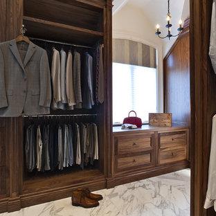 Ejemplo de armario vestidor de hombre, clásico, grande, con puertas de armario de madera en tonos medios, suelo de mármol y armarios con paneles empotrados