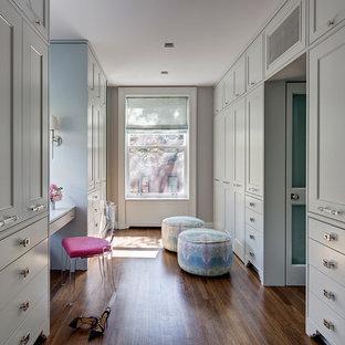 Ejemplo de vestidor de mujer, tradicional renovado, grande, con suelo de madera en tonos medios, armarios con rebordes decorativos y puertas de armario grises