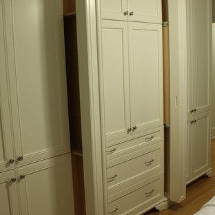 Ejemplo de armario unisex, clásico, pequeño, con armarios con paneles empotrados, puertas de armario blancas y suelo de madera en tonos medios