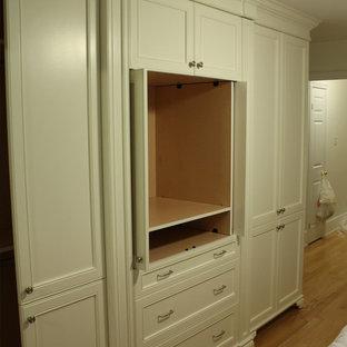 Ejemplo de armario unisex, tradicional, pequeño, con armarios con paneles empotrados, puertas de armario blancas y suelo de madera en tonos medios