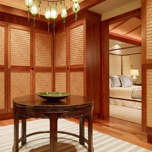 Ejemplo de vestidor tropical con armarios con paneles lisos y puertas de armario de madera oscura