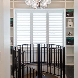 Diseño de vestidor unisex, clásico renovado, grande, con armarios con paneles lisos, puertas de armario blancas, suelo de baldosas de cerámica y suelo negro