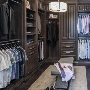 Foto de armario vestidor de hombre, clásico, con armarios con paneles con relieve, puertas de armario de madera en tonos medios, suelo de madera oscura y suelo marrón