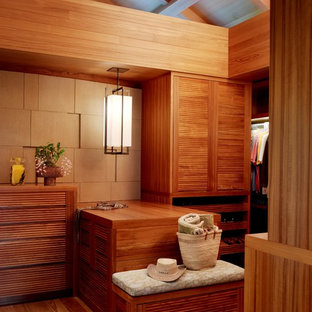 Photo of a tropical gender-neutral walk-in wardrobe in Hawaii with louvered cabinets, medium wood cabinets, medium hardwood floors and brown floor.