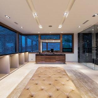 他の地域の巨大な男性用モダンスタイルのおしゃれなフィッティングルーム (オープンシェルフ、ベージュのキャビネット、ライムストーンの床、ベージュの床) の写真