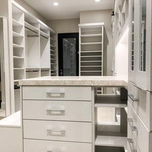 Idee per una grande cabina armadio unisex contemporanea con ante di vetro, ante in legno chiaro, moquette e pavimento beige