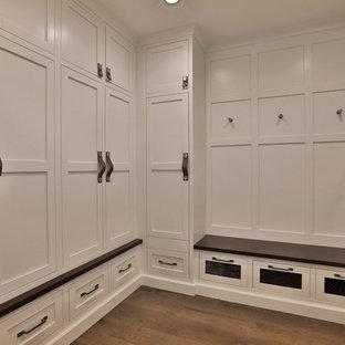 Modelo de armario y vestidor unisex, tradicional renovado, grande, con armarios con rebordes decorativos, puertas de armario blancas, suelo de madera en tonos medios y suelo marrón