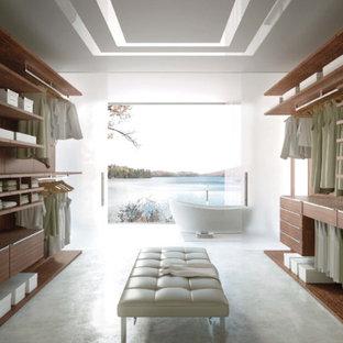 Foto de armario vestidor unisex, moderno, grande, con armarios con paneles lisos, puertas de armario de madera oscura y moqueta