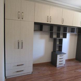 Ejemplo de armario unisex, minimalista, grande, con armarios con paneles lisos, puertas de armario beige, suelo laminado y suelo marrón