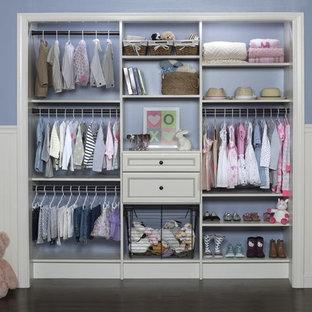 Foto de armario unisex, moderno, pequeño, con armarios con paneles lisos, puertas de armario blancas y suelo de madera oscura