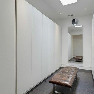 Imagen de armario vestidor unisex, minimalista, con armarios con paneles lisos, puertas de armario blancas, suelo de baldosas de cerámica y suelo marrón