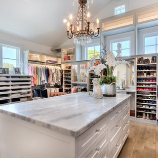 Huge farmhouse women's light wood floor walk-in closet photo in Orange County with open cabinets and white cabinets