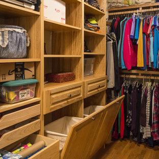 Ispirazione per una cabina armadio unisex stile americano di medie dimensioni con ante con bugna sagomata, ante in legno chiaro, pavimento in legno massello medio e pavimento marrone