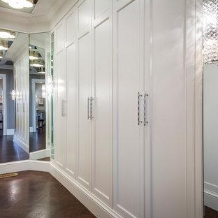 Ejemplo de vestidor unisex, minimalista, de tamaño medio, con armarios con rebordes decorativos, puertas de armario blancas y suelo de madera en tonos medios