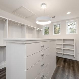 Foto de armario vestidor unisex, retro, grande, con armarios abiertos, puertas de armario blancas, suelo de madera en tonos medios y suelo marrón