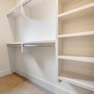 Imagen de armario vestidor unisex, vintage, de tamaño medio, con armarios abiertos, puertas de armario blancas, suelo de cemento y suelo beige