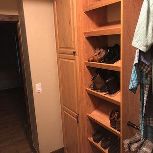 Modelo de armario vestidor unisex, tradicional, de tamaño medio, con armarios con paneles con relieve, puertas de armario de madera oscura, suelo de madera en tonos medios y suelo marrón