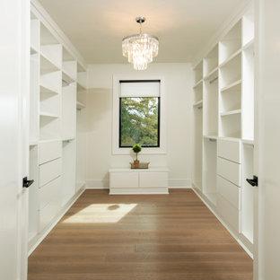 Idee per un ampio armadio incassato tradizionale con ante lisce, ante bianche e parquet chiaro