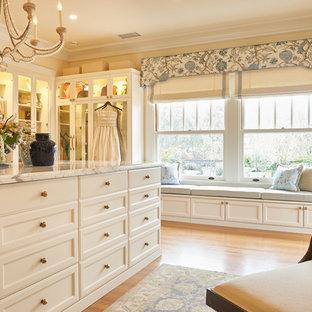 Esempio di un ampio spazio per vestirsi per donna chic con ante di vetro, ante bianche, parquet chiaro e pavimento marrone