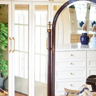 Inspiration för mycket stora klassiska walk-in-closets för kvinnor, med luckor med glaspanel, vita skåp och mellanmörkt trägolv