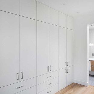 Foto de armario unisex, actual, grande, con armarios con paneles lisos, puertas de armario blancas y suelo de madera en tonos medios