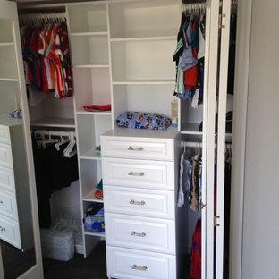 Immagine di un piccolo armadio o armadio a muro unisex minimal con ante con bugna sagomata, ante bianche e moquette
