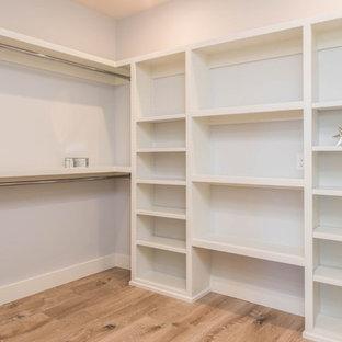 Diseño de armario vestidor unisex, clásico renovado, grande, con armarios abiertos, puertas de armario blancas y suelo de madera clara