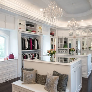 Inspiration for a large timeless women's dark wood floor walk-in closet remodel in St Louis with raised-panel cabinets and white cabinets