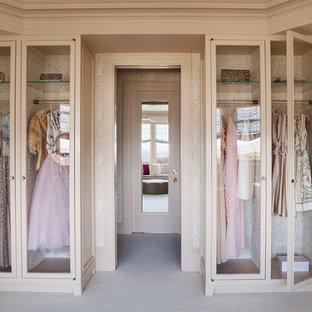 サンフランシスコの広い女性用トランジショナルスタイルのおしゃれなフィッティングルーム (ガラス扉のキャビネット、ベージュのキャビネット、カーペット敷き、ベージュの床) の写真