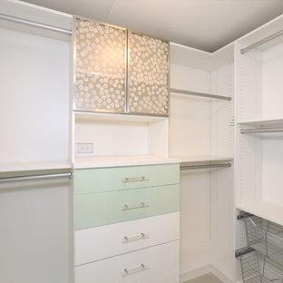 Imagen de armario vestidor actual, de tamaño medio, con armarios con paneles lisos, puertas de armario verdes, suelo de madera clara y suelo marrón