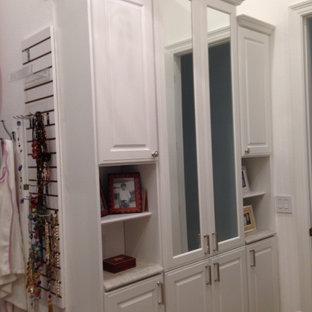 Imagen de armario vestidor de mujer, ecléctico, grande, con armarios con paneles con relieve, puertas de armario blancas y moqueta