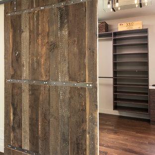 Foto di una piccola cabina armadio unisex minimalista con ante in legno bruno e pavimento in legno massello medio