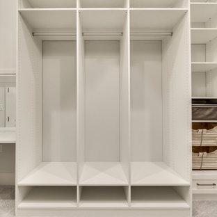 Ispirazione per un grande spazio per vestirsi unisex mediterraneo con ante di vetro, ante bianche e moquette