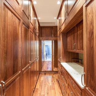 Foto de armario vestidor unisex, clásico, grande, con armarios con paneles con relieve, puertas de armario de madera oscura y suelo de madera en tonos medios