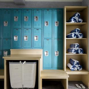 Mittelgroßes, Neutrales Klassisches Ankleidezimmer mit Ankleidebereich, blauen Schränken, Teppichboden und grauem Boden in New York