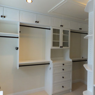 Photo of a mid-sized beach style gender-neutral dressing room in Manchester with glass-front cabinets, white cabinets and carpet.