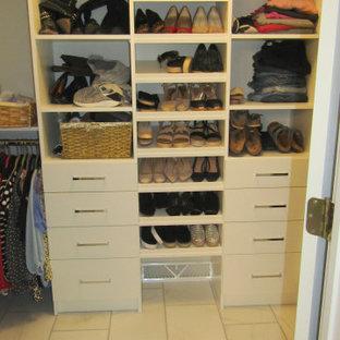 Modelo de armario vestidor unisex, clásico renovado, de tamaño medio, con armarios con paneles lisos, puertas de armario blancas, suelo de baldosas de porcelana y suelo blanco