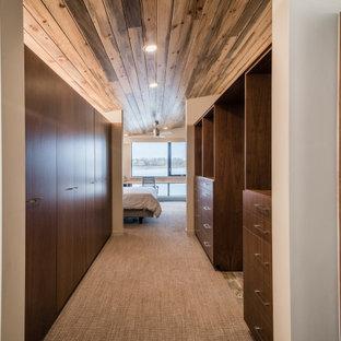 Idee per un grande spazio per vestirsi unisex stile rurale con ante lisce, ante in legno bruno, moquette e pavimento beige