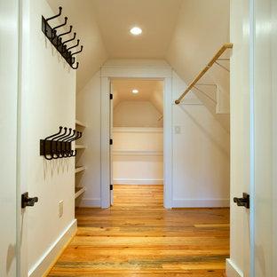 Imagen de armario vestidor unisex, rústico, con armarios abiertos, puertas de armario blancas y suelo de madera clara