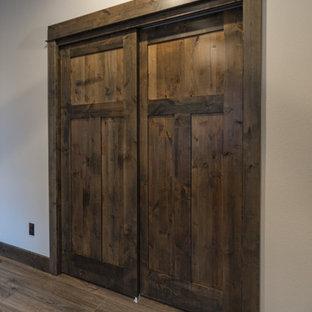 Foto de armario unisex, rústico, de tamaño medio, con suelo laminado y suelo marrón